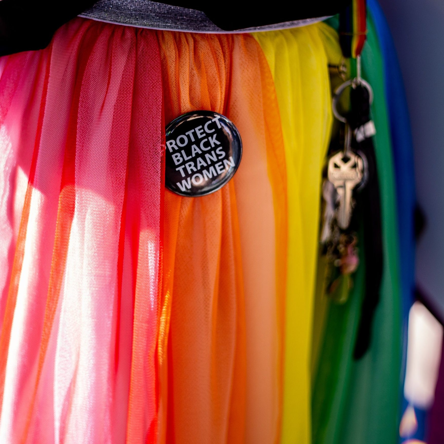 "A person wearing a rainbow skirt and a pin that says ""protect black trans women"""