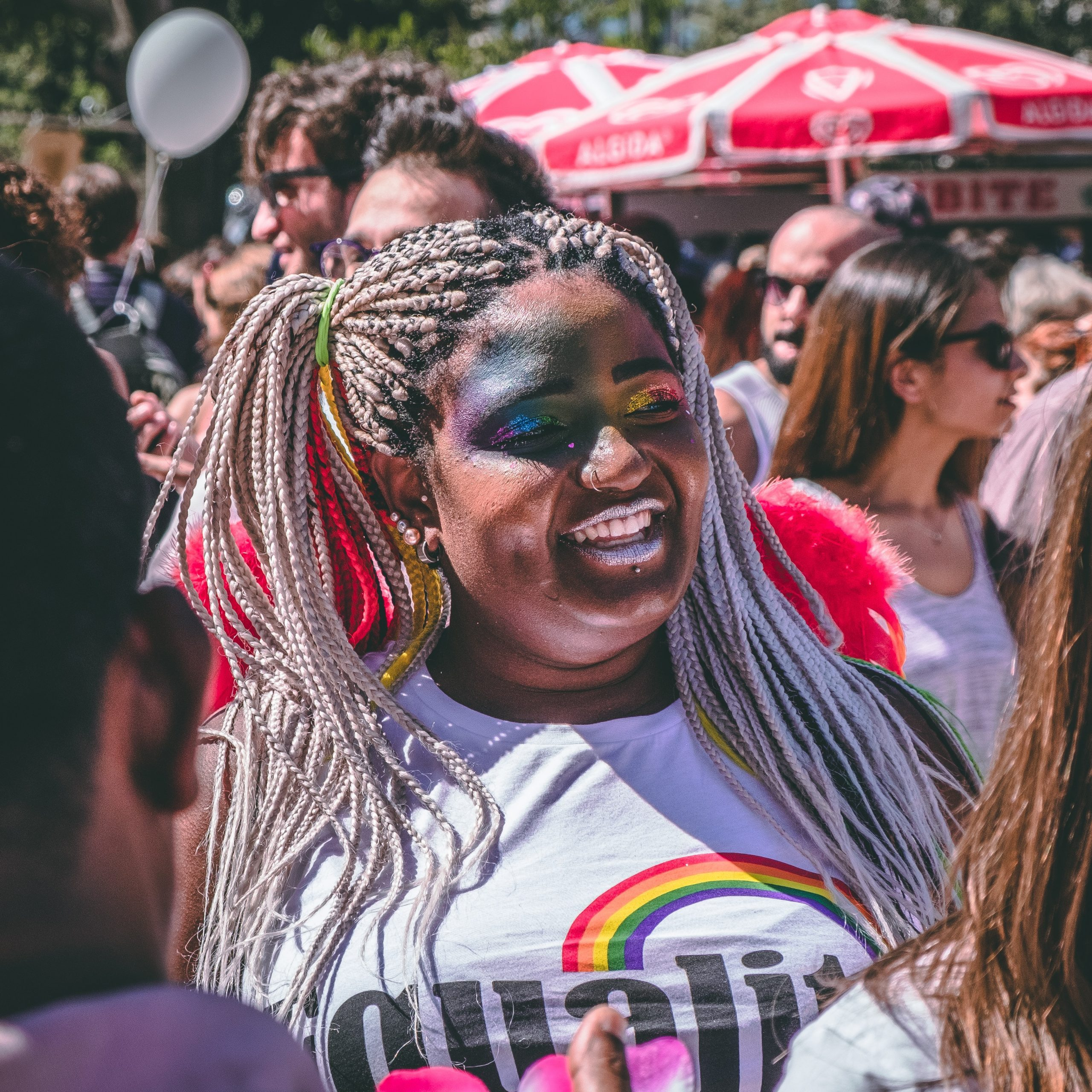 A girl in a crowd wears rainbow glitter makeup